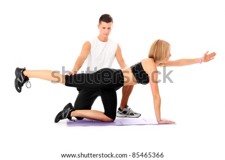 A picture of a young woman working out with her personal trainer over white background - stock photo
