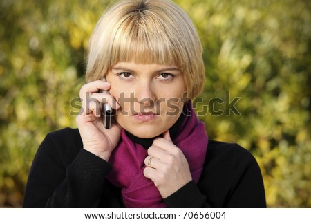A picture of an angry woman talking on the phone over natural background - stock photo