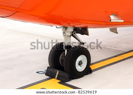 A picture of an orange undercarriage of a business jet standing on the apron - stock photo