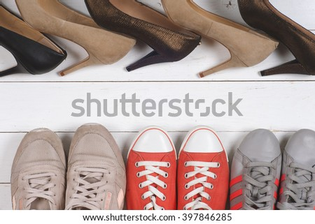 A picture of different shoes, Shot of several types of shoes, Several designs of  women shoes. Leather Shoe, Sport Shoe. Pile of various female shoes on wooden background - stock photo