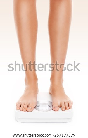A picture of female legs on bathroom scales over white background