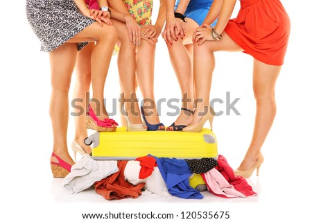 A picture of five women with their sexy legs put on a suitcase over white background - stock photo