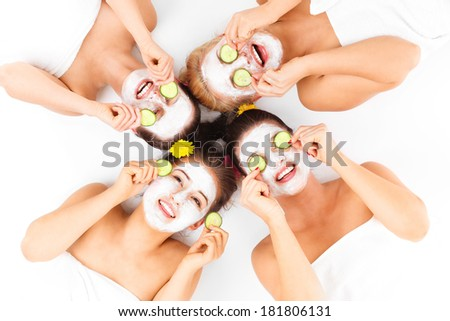 A picture of four friends enjoying their time in spa with facial masks over white background - stock photo