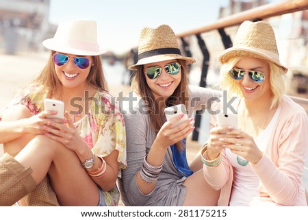A picture of group of friends using smartphones in the city - stock photo