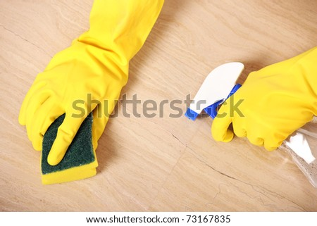 A picture of hands in yellow gloves cleaning the floor