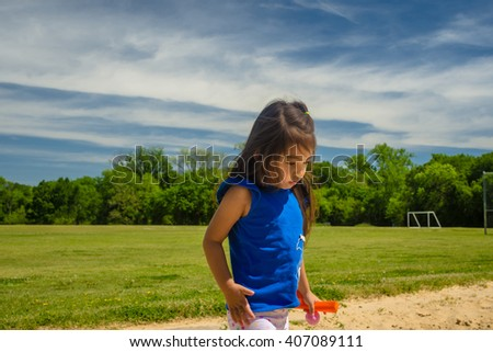 A  picture of little girl playing sand at public park,filtered color tone in picture. - stock photo