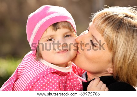 A picture of mother kissing her little girl in the park - stock photo