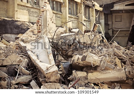 A picture of o heap of rubble and a demolished building in the background - stock photo
