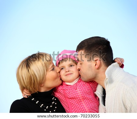 A picture of parents kissing their little girl over blue sky, a lot of space for text - stock photo