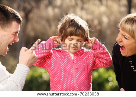 A picture of parents shouting at a little girl in the park - stock photo