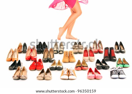A picture of sexy female legs among shoes over white background