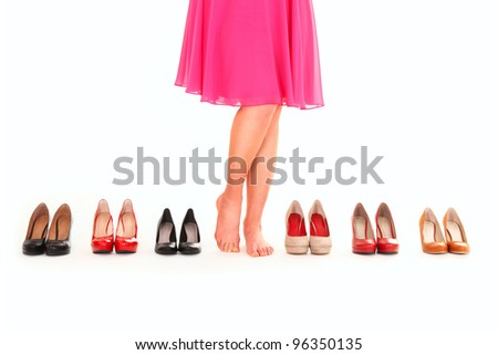 A picture of sexy female legs among six pairs of shoes over white background - stock photo