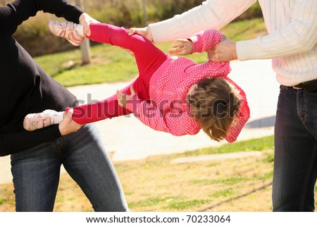 A picture of two adults fighting for an innocent child in the park - stock photo