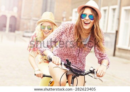 A picture of two girl friends riding a tandem bicycle in the city - stock photo