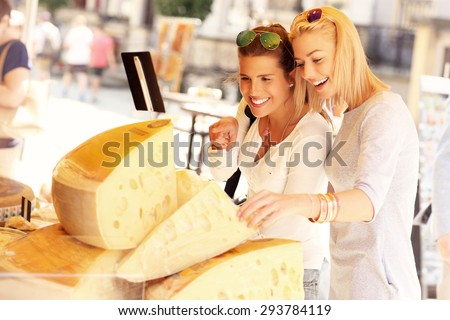 A picture of two tourists shopping for cheese on a food market - stock photo