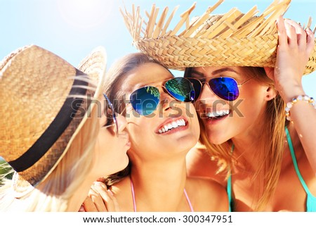 A picture of two women kissing a friend on the beach party - stock photo