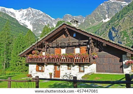 A picturesque Italian chalet in front of Italy's highest peak, the Monte Rosa, in the village of Macugnaga - stock photo