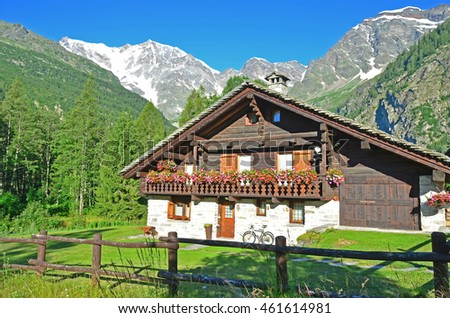 a picturesque Italian chalet in front of Italy's highest summit, the Monte Rosa, in the village of Macugnaga