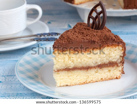A piece chocolate cream cake on a dessert plate. Behind it the whole cake and white coffee cup