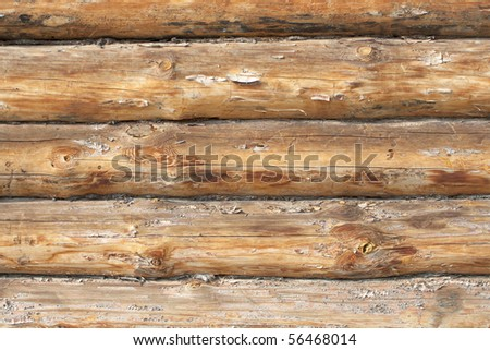 A piece of a wall in a house made of logs. Wood texture is seen distinctly - stock photo