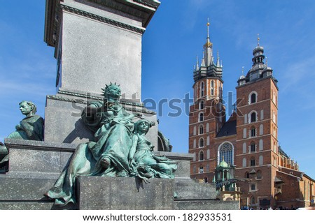 A piece of Adam Mickiewicz statue with a Mariacki church in the background on main Market Square in Cracow, Poland