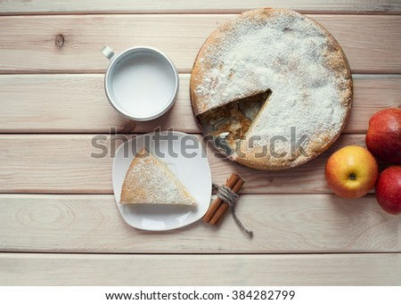 A piece of apple pie and cup of milk on a wooden table. Apple pie, cinnamon sticks and red juicy apples. Top view. - stock photo