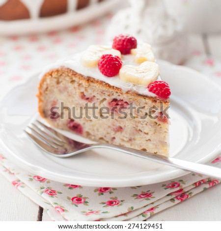 A Piece of Banana Cake with Sugar Glaze Topped with Raspberries and Banana Slices, square, close up, shallow dof - stock photo