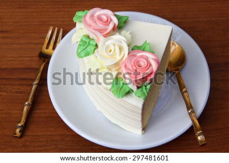 a piece of cake.Tasty soft creamy butter cake on a white plate over wooden background. tree pink white creamy roses decorated on top of butter cake.   - stock photo