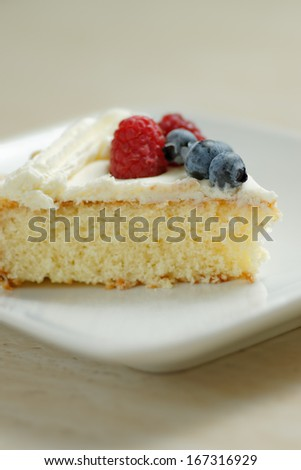 A piece of cake with cream and berries - stock photo
