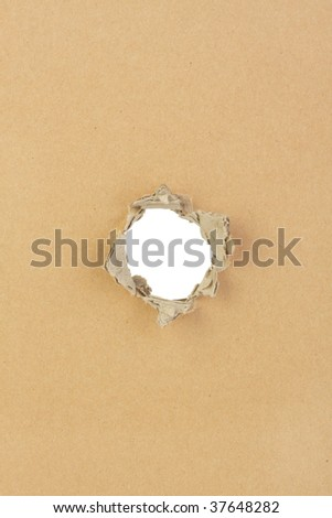 A piece of cardboard with a hole ripped through the middle, white space background with plenty of copyspace. - stock photo