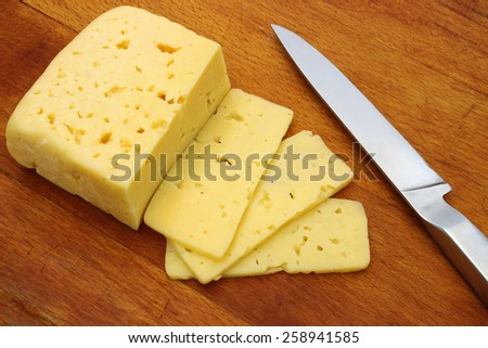 A piece of cheese and a knife on a cutting board - stock photo
