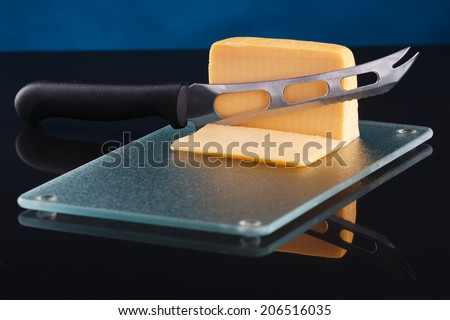 a piece of cheese on a glass cutting board with a knife - stock photo