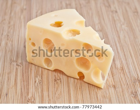 a piece of cheese with holes on a wooden board - stock photo