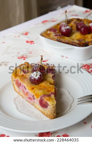A piece of cherry pie on the white plate. A cherry pie in the ceramic mold  in the background - stock photo