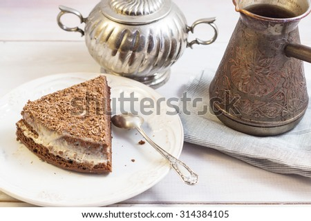 A piece of chocolate cake on a white plate. Turk with hot coffee, napkin and silver spoon. Breakfast in coffee house