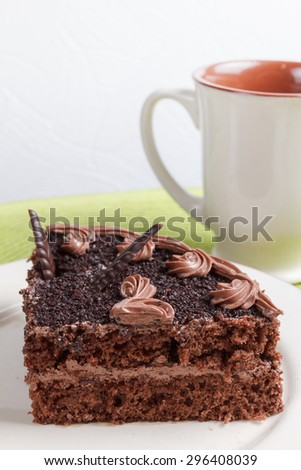 A piece of delicious chocolate sponge cake with cream on a plate and a cup of aromatic tea - stock photo