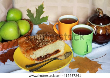 A piece of fresh baked homemade cabbage pie (tart, pasty, cake, kulebyaka) with sesame on the yellow plate serving with red tomatoes, green apples, pumpkin, two cups of tea, foliage and vintage forks - stock photo
