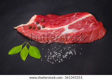 A piece of fresh meat with basil and salt lies on the black desk - stock photo