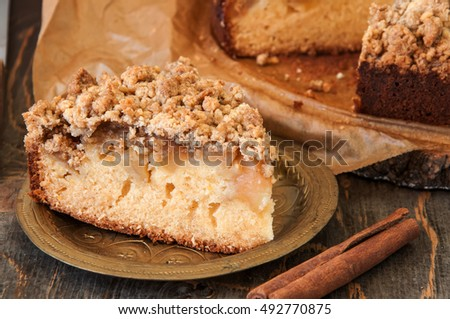 A piece of Freshly baked Cinnamon Cardamom apple crumble pie or Cake on vintage golden plate on wooden background with cinnamon stick near. Rustic style. Close up. Horizontal view.