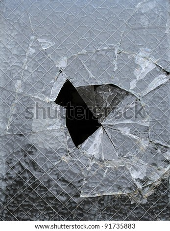 a piece of glass window with a cracked hole - stock photo