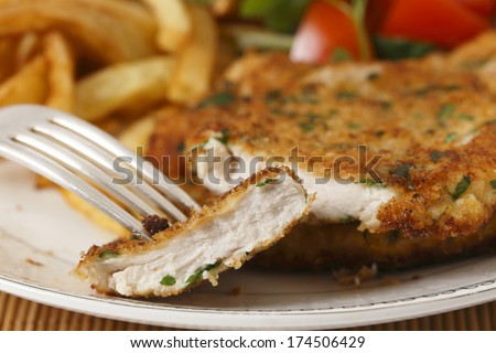 A piece of homemade breaded chicken schnitzel or escalope on a fork with french fries and a tomato and green salad behind