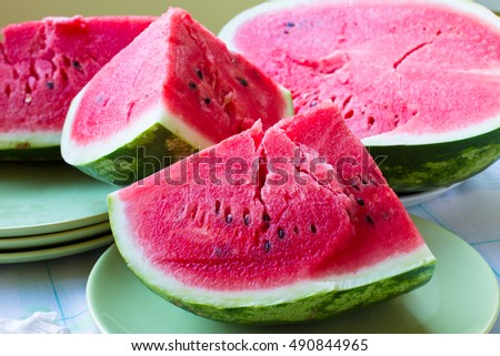 A piece of juicy ripe watermelon with fleshy pink flesh on a light green plate. Juicy and useful fruit dessert.