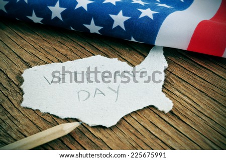a piece of paper in the shape of United States with the word Veterans Day on a wooden background with the flag of the United States in the background - stock photo