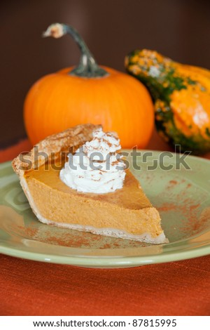 A piece of pumpkin pie on a green plate. - stock photo