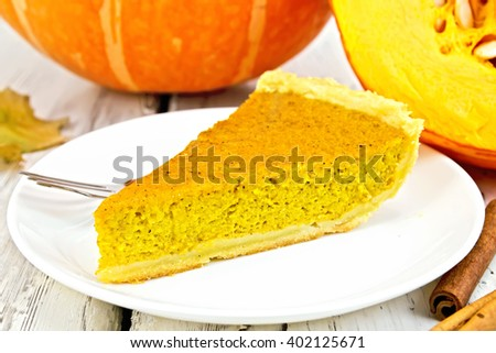 A piece of pumpkin pie with whipped cream, a fork in the white plate, gourd and cinnamon on a background of bright wooden planks - stock photo