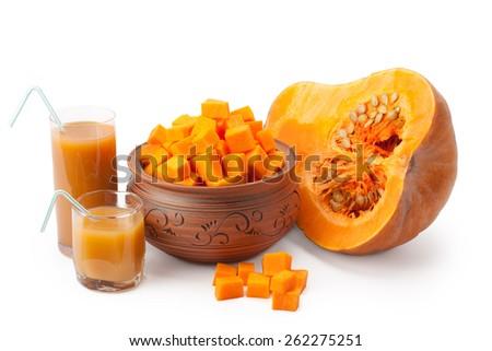 a piece of pumpkin, pumpkin cubes in a clay pot and pumpkin juice - stock photo