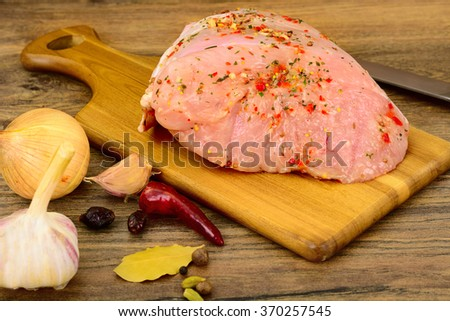 A Piece of Raw Turkey in Spices for Grilling on Woody Background. Studio Photo - stock photo