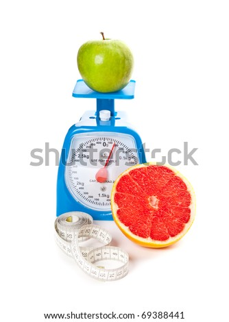 A piece of red grapefruit, an apple, measure tape and scale isolated on white