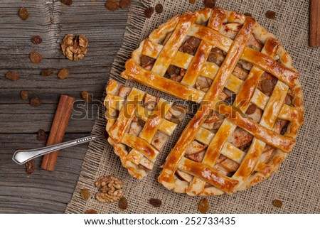 A piece of sliced apple pie with a metal spatula on vintage wooden background texture. Top view - stock photo