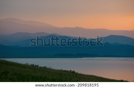 A piece of the lake and the silhouettes of hills, lit by the setting sun. - stock photo